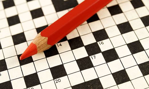 Red pencil crayon on top of crossword puzzle