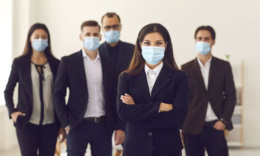 Responsible young company manager with group of workers all wearing face masks at work