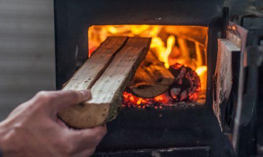 Man putting log to wood burning stove