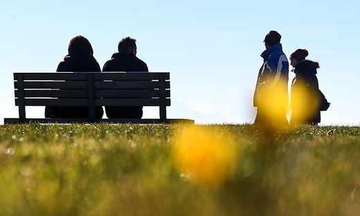 Ein Paar sitzt am Ufer des Bodensees auf einer Bank
