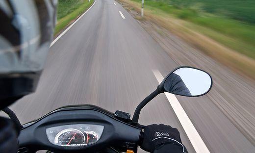 Eine Bikerin rutsche mit ihrem Motorrad auf glattem Asphalt aus