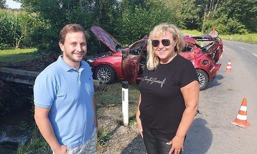 Sandra Mocnik mit Philipp Landgraf, einem ihrer Lebensretter. Hinten das Auto, das im Bach (links) landete