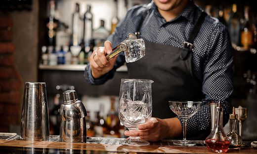 Bartender putting a big ice cube into the glass with help of special ice tongs
