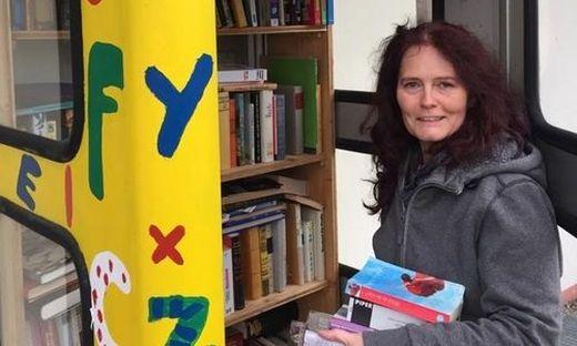 Beatrix Altendorfer beim Nachbestücken eines offenen Bücherregals