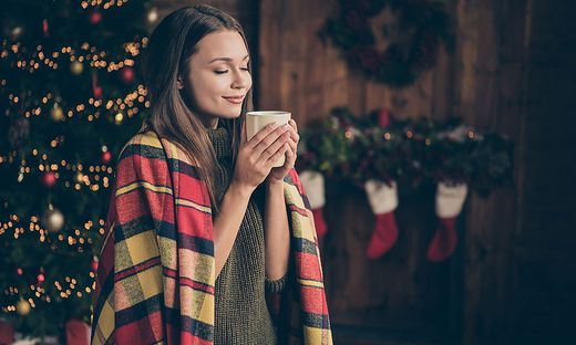Profile side photo of dreamy positive woman covered checkered blanket feel pleasure on christmas time vacation hold mug smell hot beverage in house with x-mas ornament wreath red socks indoors