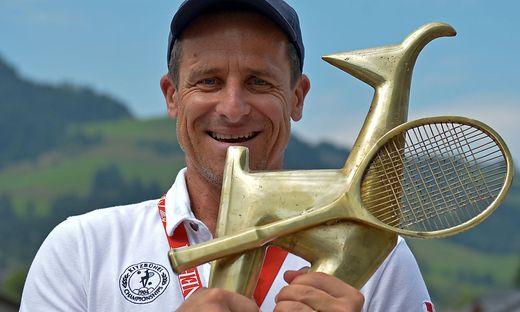 Der Kitzbühel-Turnierdirektor hält die begehrte Gams, die Siegertrophäe in der Hand