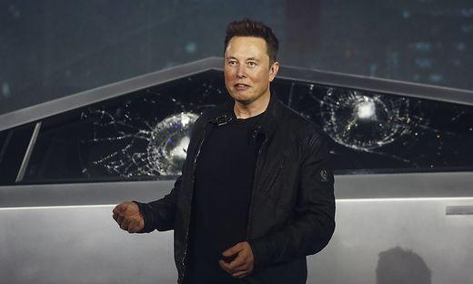 Tesla-Chef Elon Musk musste die Präsentation mit den beschädigten Scheiben im Hintergrund fortsetzen