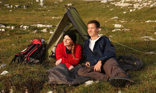 Junges Paar schaut beim Zelten in den Bergen dem Sonnenuntergang entgegen