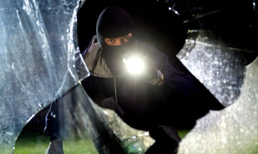 Einbrecher mit Taschenlampe hinter einer eingeschlagenen Fensterscheibe