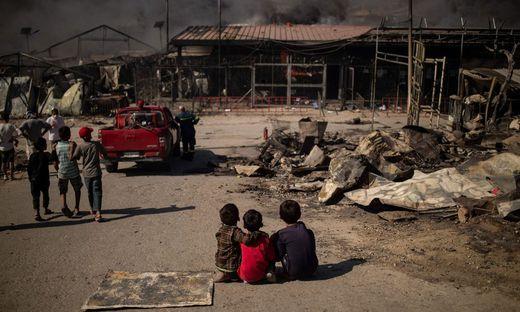 Kinder sitzen im abgebrannten Flüchtlingslager von Moria
