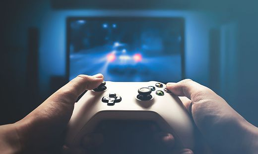 Video gaming console. Man playing car racing