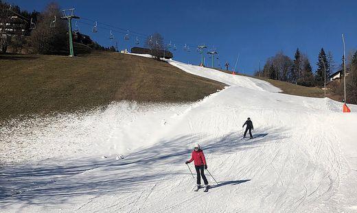 Weißes Band im grünen Gras: Während am Berg genug Schnee liegt, konnte man in Bad Kleinkirchheim die Talabfahrten und die Loipe nur mit Kunstschnee eröffnen