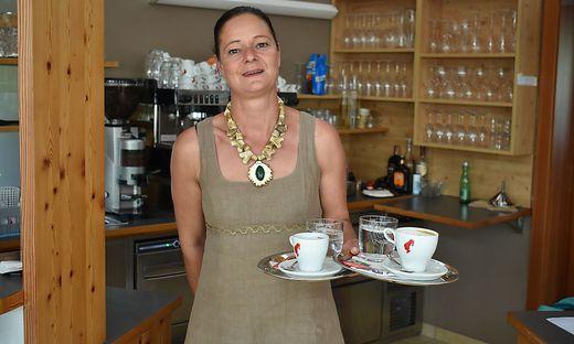 Die Wirtin in ihrem Lokal mit zwei Kaffeetassen in der Hand