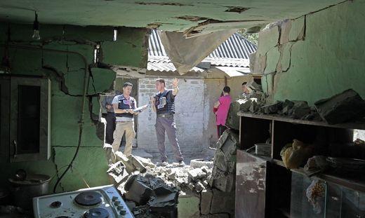 OSZE-Beobachter dokumentieren in einem Wohnviertel der ostukrainischen Stadt Dokutschajewsk Kriegsschäden