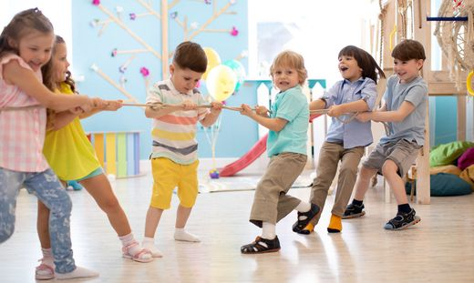 group of kids play and pull rope together in daycare