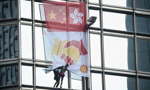 Robert entrollte ein Banner, das die Flaggen Chinas und Hongkongs sowie zwei sich schüttelnde Hände zeigt