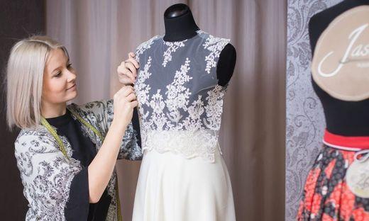 Schneiderin, die an einem weißen Spitzen-Brautkleid arbeitet