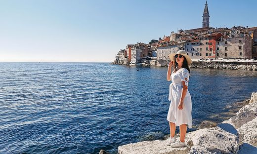 Side view of woman standing on rock by sea, looking at picturesque seaside town of Rovinj, Croatia.