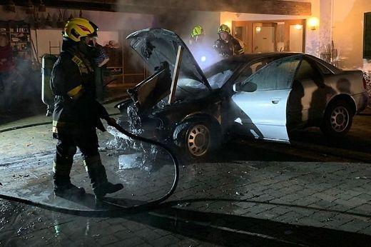 Einsatzkräfte löschen Brand in Auto, es steigt noch Rauch auf