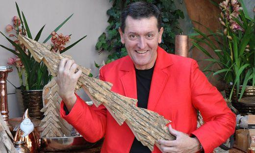 Seppi Rukavina im roten Sakko, hält einen aus Holz geschnitzten Christbaum wie eine Gitarre