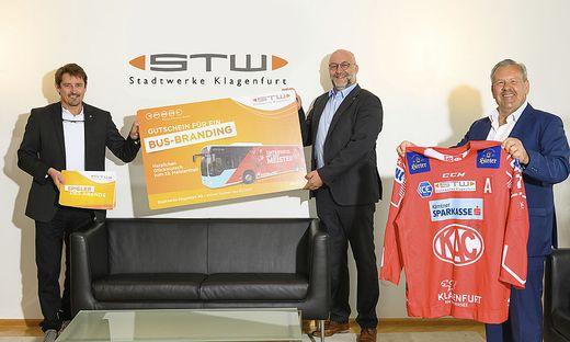 KAC-Geschäftsführer Oliver Pilloni freut sich über den Gutschein für ein Busbranding, der ihm von Erwin Smole und Andreas Waldher überreicht wurde.