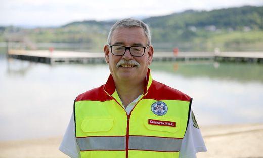 Kurt Komarek in der Uniform der Wasserretter. Hinter ihm der Längsee