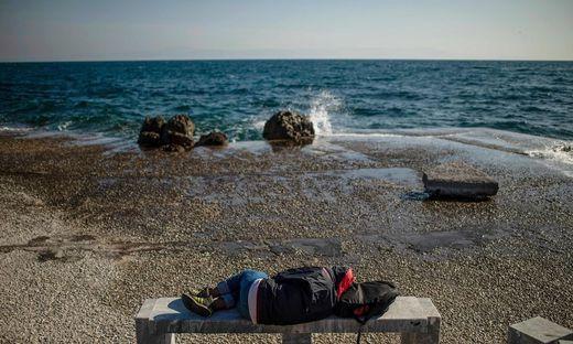 Ein Migrant schläft auf der ostägaischen Insel Lesbos auf einer steinernen Bank am Meer