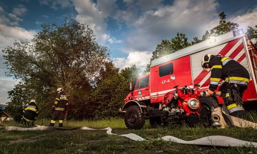 Vor einem Feuerwehrauto verlegen Feuerwehrleute einen Wasserschlauch