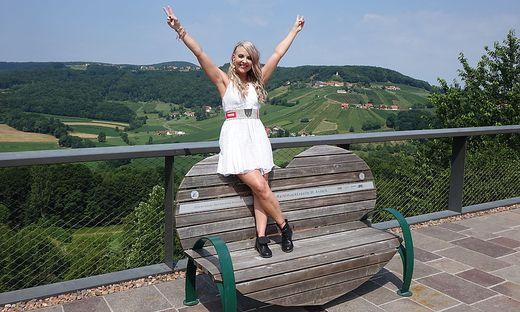 Hannah auf einer Herzbank sitzend mit der Region im Hintergrund