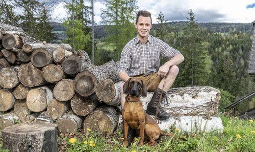 Bauer Manuel sitzt auf einem Holzstoß, vor ihm sein Hund, ein Jagdhund