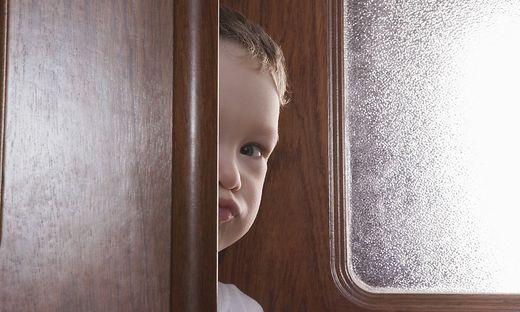 Young boy peeks round wooden door frame