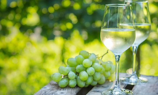 Zwei Weingläser und Weintrauben am Tisch liegend