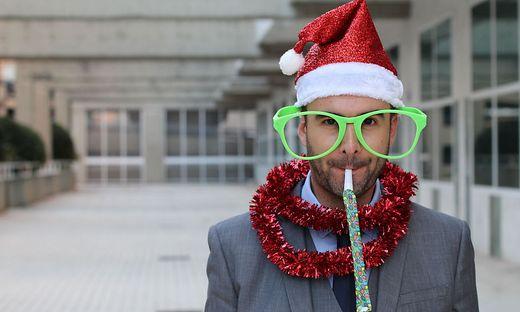 Ein junger Mitarbeiter auf der Weihnachtsfeier mit Nikolausmütze
