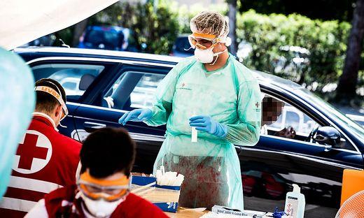 Vier Rot-Kreuz-Mitarbeiter arbeiten bei der Drive-in-Teststation in Klagenfurt