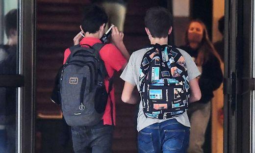 Kinder mit Maske vor Schule