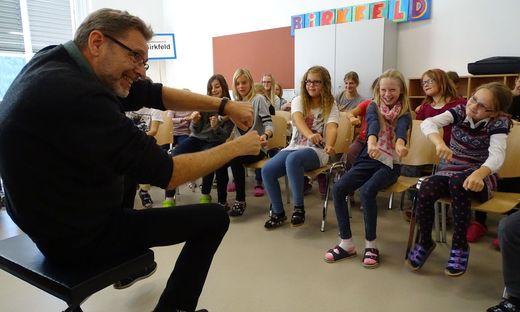 """Muntermacher: Franz Herzog """"fährt"""" mit der Klasse durch die Schule, die Kinder lenken mit"""