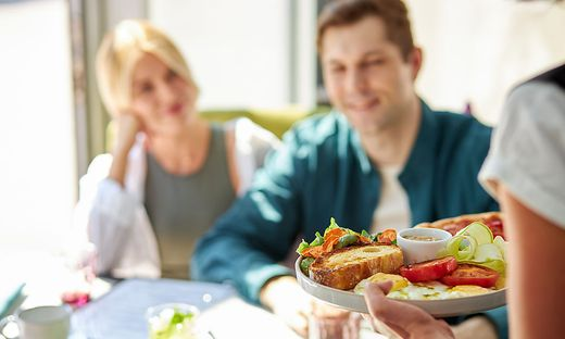 the waiter delivers salad to guests sitting in cafe