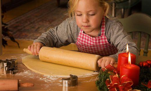 Kind baeckt zu Weihnachten im Advent Plaetzchen
