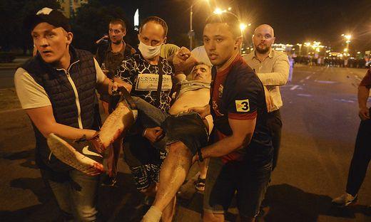 Protestierende helfen einem Verwundeten - Beamte gingen mit Schlagstöcken auf die Demonstranten los