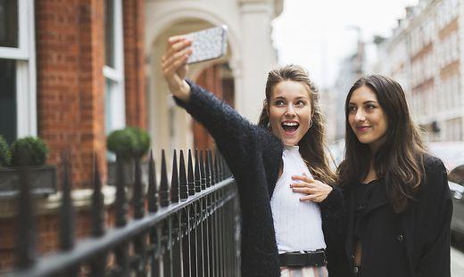 Cool fancy girls in London smily selfie