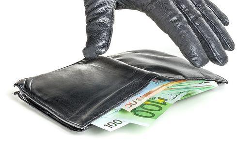 Dieb mit Lederhandschuh greift nach einem Geldbeutel