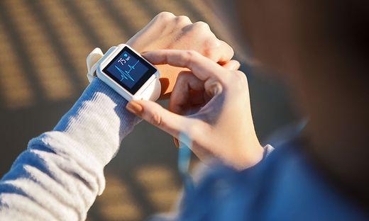 Der Blick auf den Fitnesstracker: ein Fünftel der Österreicher verwendet Smartwatches und Fitness-Apps