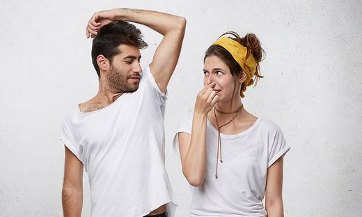 Female having disgusted look covering her nose with hand while smelling her husband`s armpit. Bearded man having nasty smell from sweat after running showing his wet underarm. Unpleasant smell