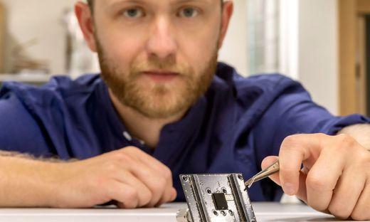 Paul Maierhofer mit dem Ergebnis seiner Dissertation: dem 12 mal 9 mal 3 Millimeter kleinen Partikelsensor.