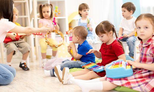 Teacher and cute kids during music lesson in preschool