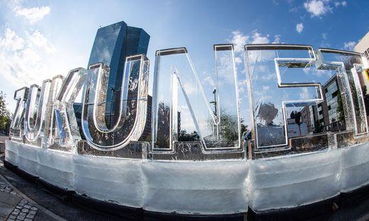 """Greenpeace-Aktivisten formten das Wort """"Zukunft"""" aus Eis-Buchstaben. Im Hintergrund: die EZB-Zentrale"""