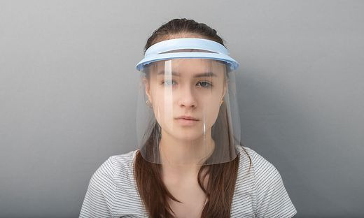 Young woman in a protective mask screen with a visor on a gray background