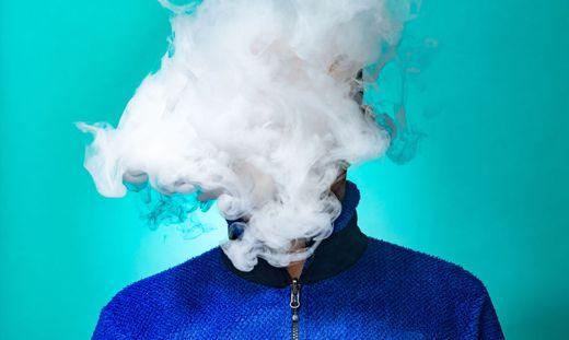A masked man smoking vape and exhaling