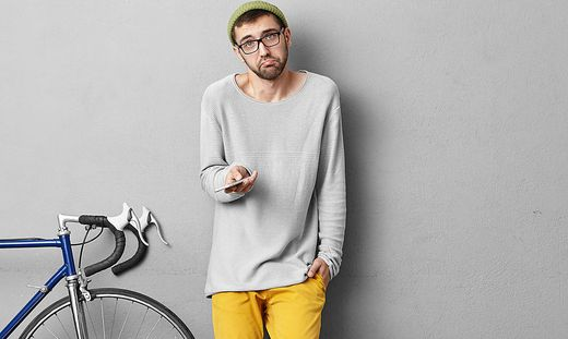 People, lifestyle and modern urban lifestyle concept. Picture of clueless young bearded European man holding gadget and shrugging shoulders, feeling confused while having problem with connection