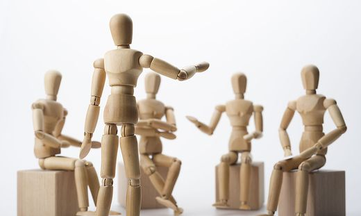 Holzfiguren, die einen Vortrag darstellen